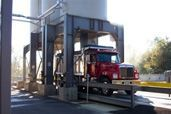 Silos empty contents into trucks while they are weighed
